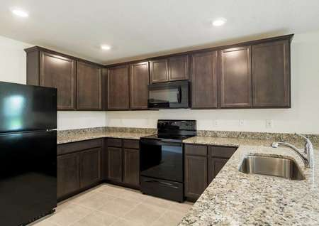 Estero floor plans kitchen with recessed lighting, all black kitchen appliances and dark brown crown molding cabinets.