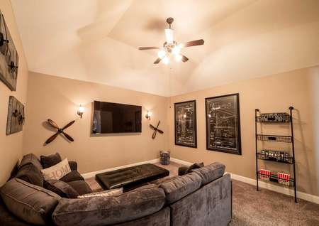 Media room with carpet, ceiling fan and large sectional.