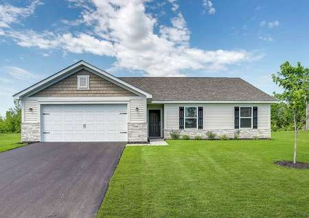 Aitkin finished house with green grass, paved driveway, and white carriage style garage door