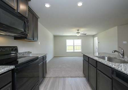 Trinity kitchen with dark custom cabinetry, canned lights in the ceiling, and granite countertops