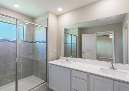 The Tuscany floor plans bathroom has a walk-in shower,white cabinetry and quartz countertops.