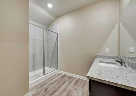 The master bathroom in the Texoma floor plan with granite countertops, wood-like flooring and a walk-in shower.