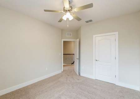 Carpeted bedroom with a ceiling fan and a large closet.