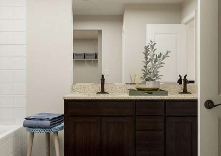 Rendering of the master bathroom focused   on the double-sink vanity with brown cabinets. The shower is visible ot the   left.