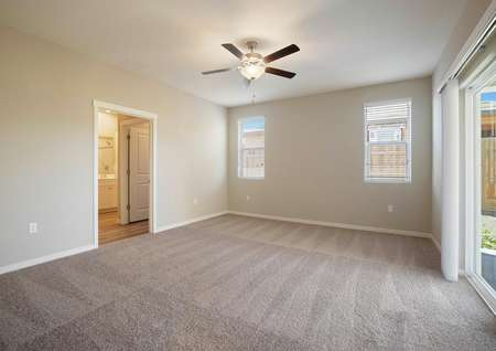 The master suite has light brown carpet, tan walls and a ceiling fan.