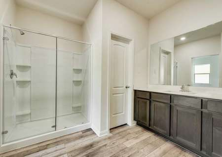 The master bath has a large glass enclosed shower and spacious vanity.