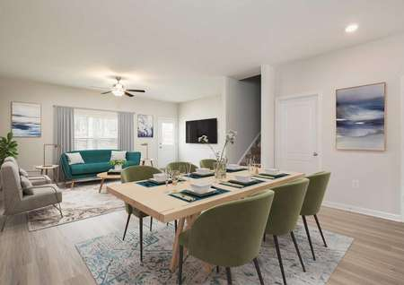 Open-concept dining and living room decorated with mid-centry modern table chairs rugs, ceiling fan and window.