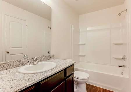 Chippewa bathroom with granite counters, brown cabinets, and white fixtures