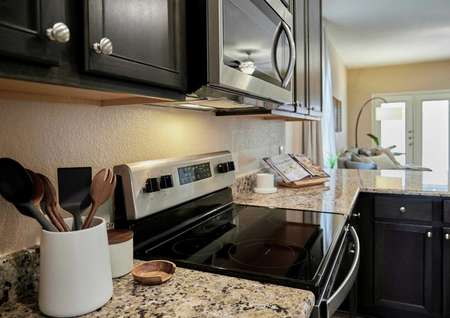Stainless kitchen appliances and dark cabinets with utensil holder and cook book