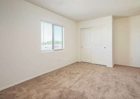 The Luna floorplan offers a second carpeted bedroom with a window with blinds.