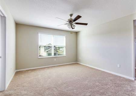 The master bedroom upstairs in the St. Johns floor plan that has light brown carpet, tan walls, and a ceiling light fan.