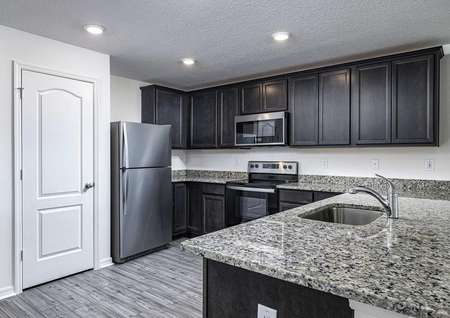 Open-concept kitchen with installed appliances, upper-wood cabinets and large granite countertops