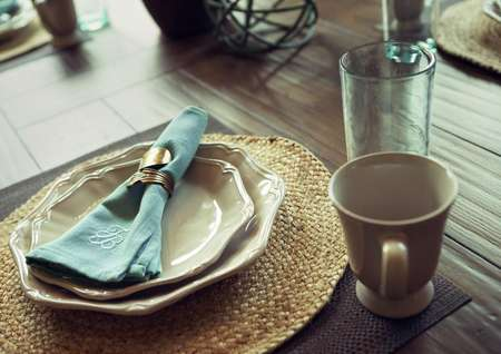 Dining table detail with coffee cup, plates and napkin.
