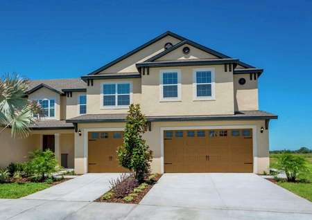 Exterior view of the two-story Tuscany floor plan that has tan paint and a decorative orange garage.