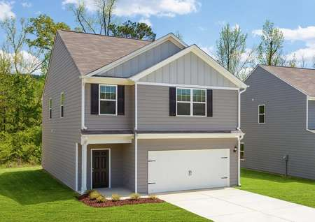 Beautiful, two-story home with a long driveway, a two-car garage and a covered front porch.