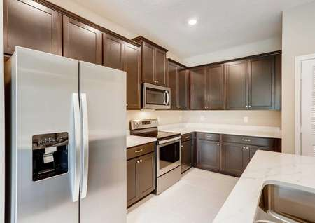 Fully upgraded kitchen in the Mateo model. Quartz countertops, stainless steel appliances, dark brown cabinetry and kitchen pantry