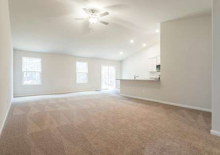 Living room with carpet and ceiling fan. Overlooking kitchen with breakfast bar and white cabinets.