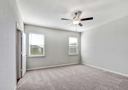 Jasper bedroom with light color carpeting, white frame windows, and overhead ceiling fan