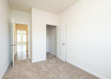 Spare bedroom on main level of home with carpet, walk-in closet, hallway leads to dining room.
