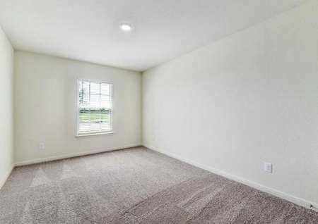 Medina bedroom with can light, white on white walls, and brown carpeting
