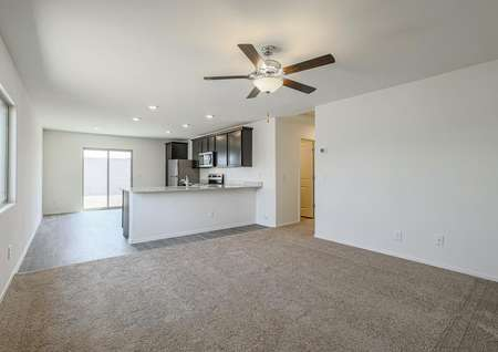 Open family room with tan carpet, a ceiling fan and access to the kitchen.