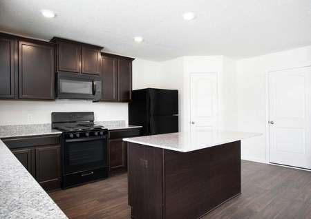 Pennington kitchen with brown cabinets, can lights, and light colored granite