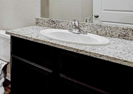 Fannin bathroom with granite vanity and brown cabinet, white toilet, and white shower