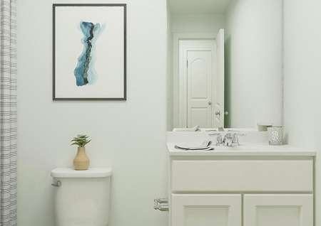Rendering of a full bath showing a white   cabinet vanity, toilet and shower hidden behind a striped curtain. The space   is decorated with a candle, potted plant and abstract art.