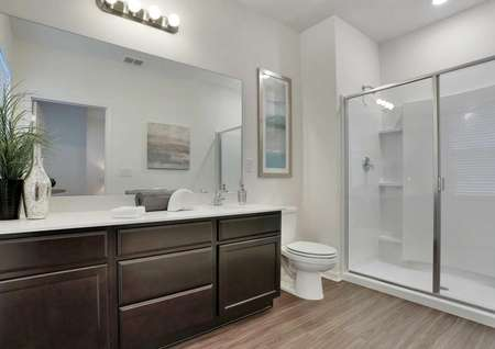 The master bathroom with white walls, brown cabinets and a walk-in showerin the Pine Key floor plan