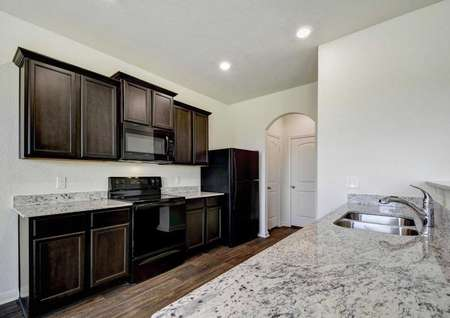 Mesquite kitchen with granite tops, black appliances, and wood flooring