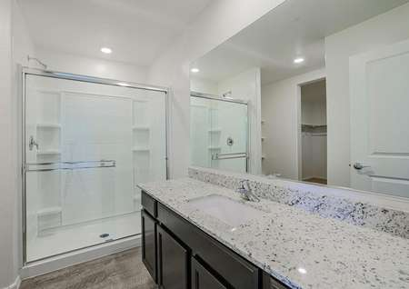 Gorgeous master bathroom with white-tiled shower and an incredible vanity with granite countertops.