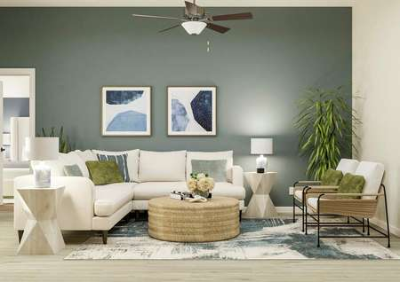 Rendering of the spacious living room   with light wood-look flooring, a blue accent wall and a ceiling fan. The room   is decorated with a white sectional couch, two end tables, a coffee table and   two armchairs.