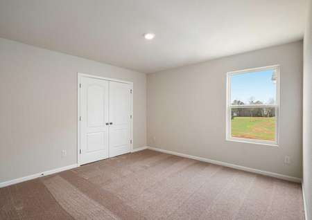 Ashley bedroom with white French doors, large window, and light brown carpeting