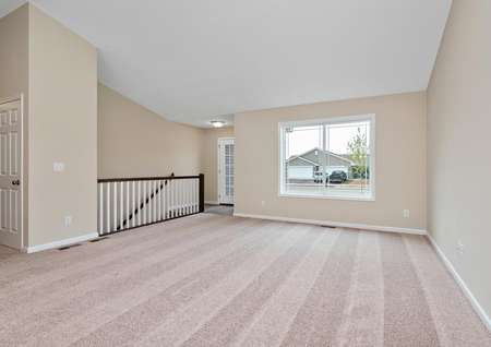 Spacious living room with carpet and window overlooking the front yard.