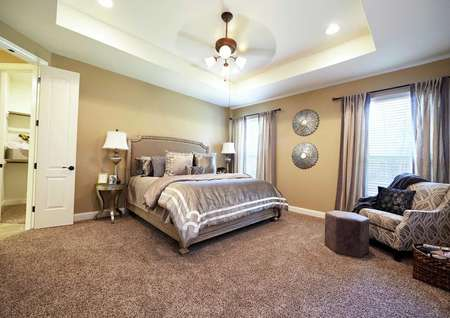 Kingston bedroom withfurniture including large bed, sitting chair, and wall hanging art