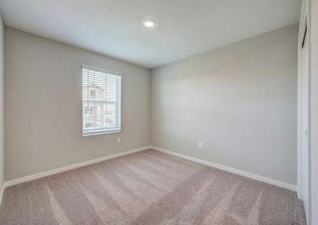 A secondary bedroom upstairs in the Kennedy floor plan with carpet floors, white baseboards and tan walls.