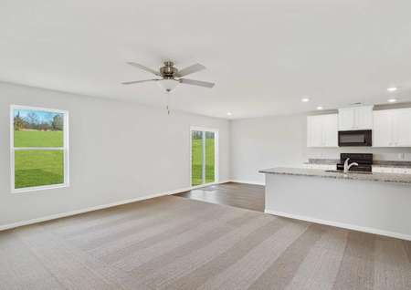Burke great room with ceiling fan, tan carpets, and white-finished kitchen