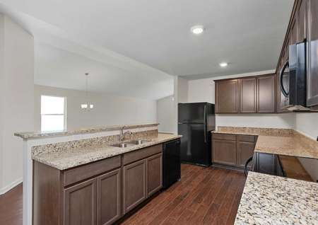 The Clairborne kitchen side view shows the large granite countertops with stainless steel sink, black appliances, light brown cabinets with crown molding, and vinyl wood like flooring