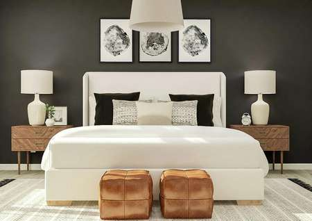 Rendering of the spacious master suite in   the Jordan floor plan. The room has a large cream bed and two wooden   nightstands against a dark accent wall. The wood-style flooring is covered by   a black-and-white rug.