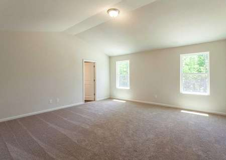 Fripp master bedroom with large windows, tan carpet, and vaulted ceilings