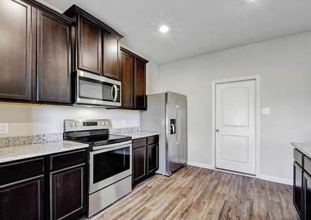 Carson completed kitchen with stainless steel appliances, dark wood cabinets, and gray granite counters