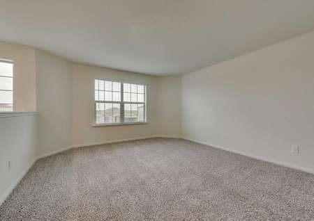 Game room in the Oakmont model with carpet flooring and large exterior window with 2