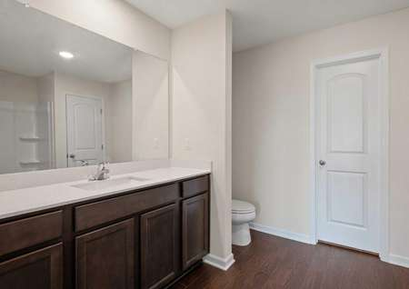 The master bathroom of the Blanco model with dark brown cabinets, white quartz countertops, full mirror, with separating wall in between the sink and toilet and vinyl flooring throughout with white door