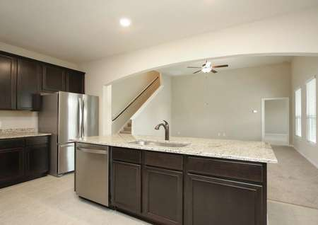 View from kitchen overlooking island with granite into spacious living room with ceiling fan, three windows, side of staircase, dark cabinets, tile floor in kitchen.