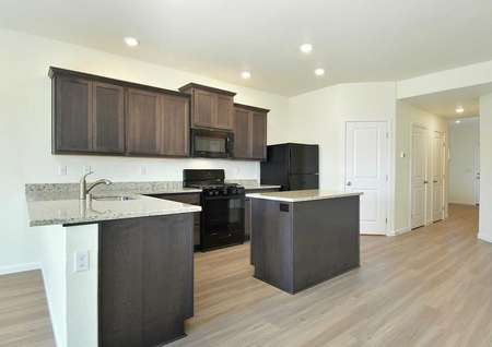 The Northwest Oak offering another view of the kitchen showing granite countertops and black appliances.