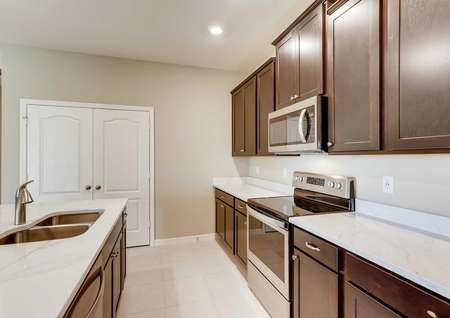 The Santa Maria model home's kitchen with dark brown cabinetry, crown molding, tile flooring and stainless steel appliances