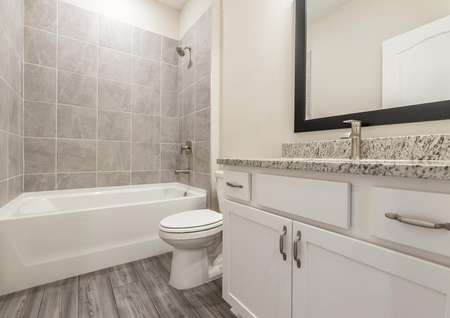 Secondary bathroom with granite countertops and modern hardware.