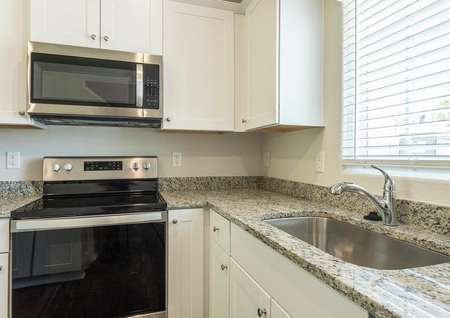 Maple kitchen with granite countertops and white cabinets.