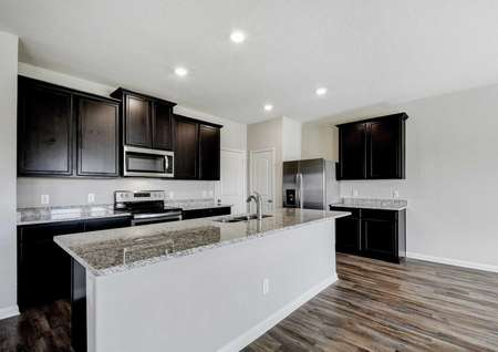 Shelby kitchen with recessed lights, large granite island with undermount sink, and brown cabinetry