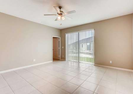 Open living room with tile flooring in the Mateo model home. Open blinds show the sliding glass back door